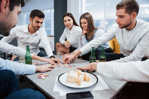 Отдых с игрой. празднование успешной сделки. молодые офисные работники сидят возле стола с алкоголем