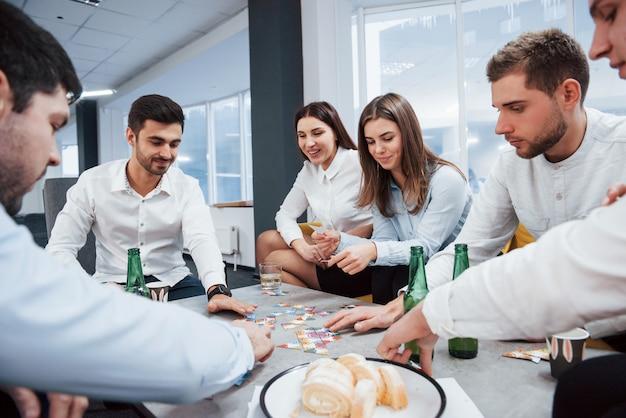 Отдыхать после тяжелого дня. отдых с игрой. празднование успешной сделки. молодые офисные работники сидят возле стола с алкоголем
