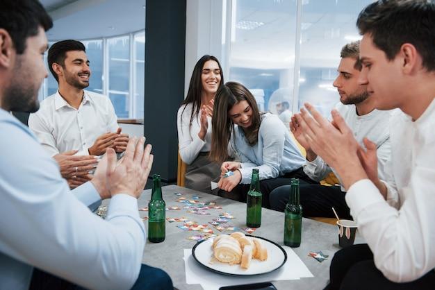 Хорошая шутка. празднование успешной сделки. молодые офисные работники сидят возле стола с алкоголем
