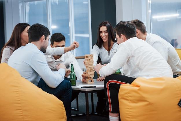 Приятный вечер в хорошей компании. празднование успешной сделки. молодые офисные работники сидят возле стола с алкоголем