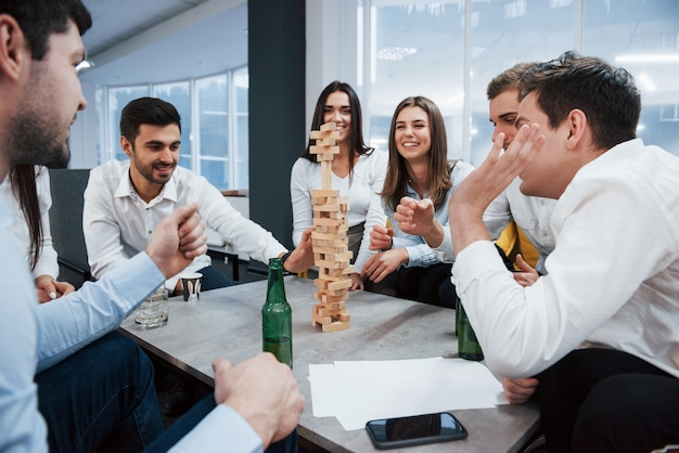 Будьте осторожны, пожалуйста. празднование успешной сделки. молодые офисные работники сидят возле стола с алкоголем