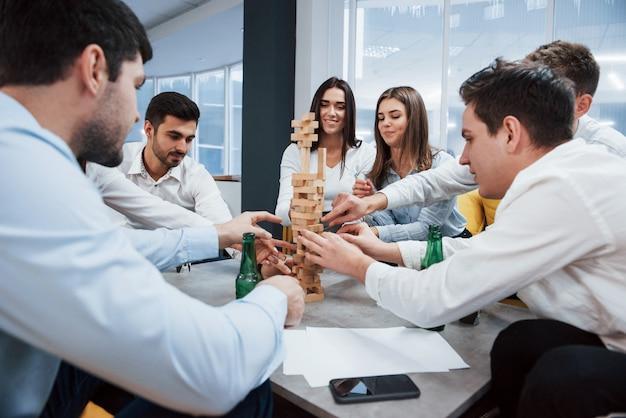 Это почти падение. празднование успешной сделки. молодые офисные работники сидят возле стола с алкоголем