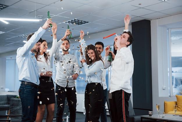 それが成功の様子です。モダンな照明付きのオフィスで飲み物を押しながら成功を祝うクラシックな服装の若いチームの写真