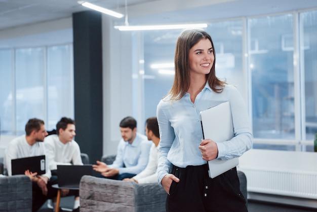 Брюнетка влюблена в свою работу. портрет молодой девушки стоит в офисе с сотрудниками на фоне