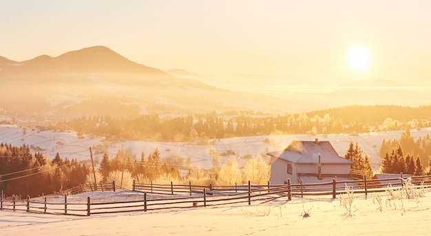 神秘的な冬の風景は冬の雄大な山々です。幻想的な夕日。雪の中で家を録音します。写真礼儀はがき。カルパティア人