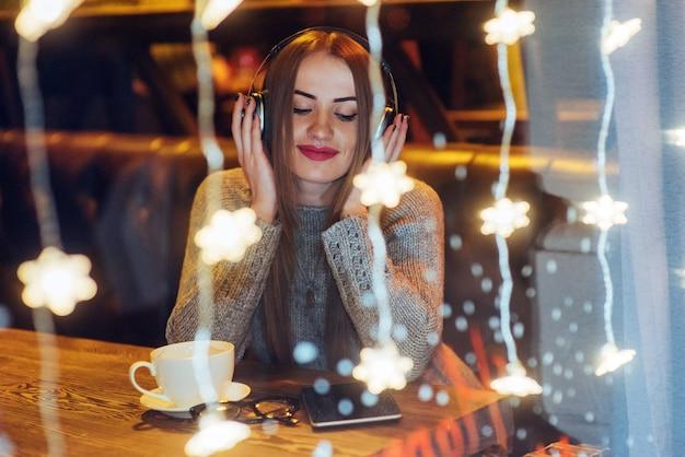 カフェに座って、コーヒーを飲む若い美しい女性。音楽を聴くモデル。クリスマス、新年、バレンタインデー、冬休み