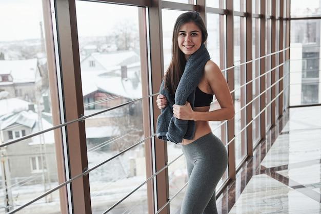 С полотенцем на шее. великолепная брюнетка в спортивной одежде позирует в тренажерном зале возле окна