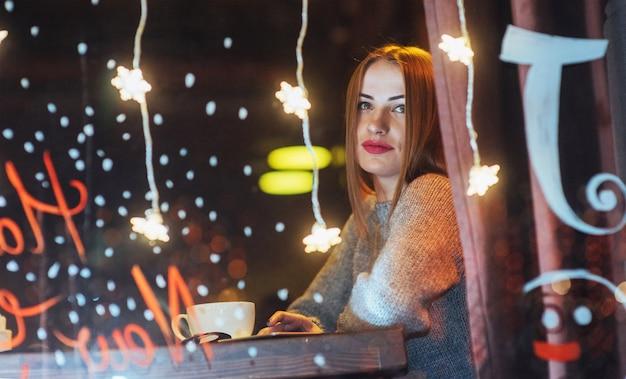 カフェに座って、コーヒーを飲む若い美しい女性。クリスマス、新年、バレンタインデー、冬休み
