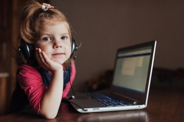 Маленькая девочка с наушниками слушает музыку, используя ноутбук