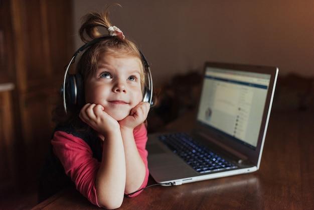 音楽を聞くヘッドフォンで幸せな美しい子