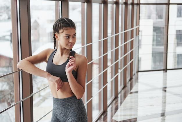 Брюнетка в спортивной одежде позирует и кладет на перила возле окна в спортзале