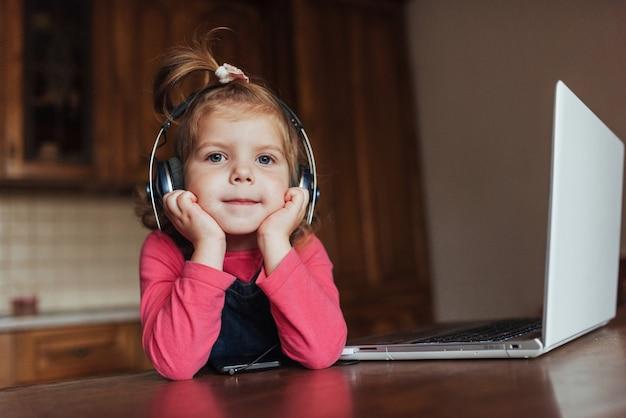 Счастливый красивый ребенок в наушниках слушает музыку.