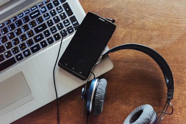 Ноутбук и гарнитура телефон на столе.