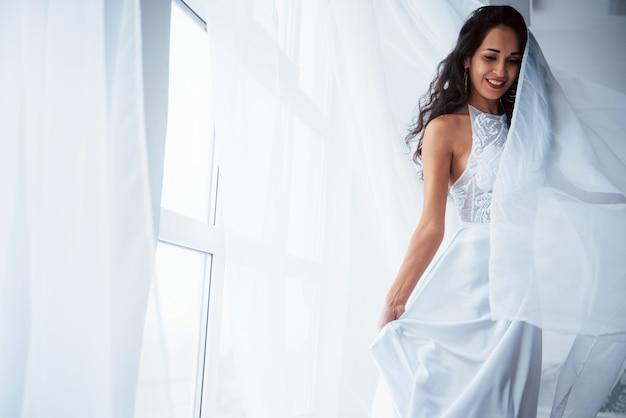エレガントな服。白いドレスを着た美しい女性が窓から日光の下で白い部屋に立っています。