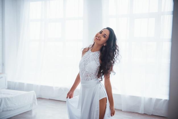 満足して無料。白いドレスを着た美しい女性が窓から日光の下で白い部屋に立っています。