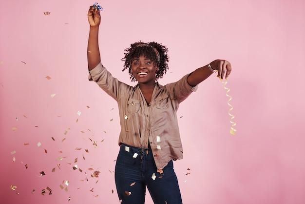 子供のように幸せ。紙吹雪を宙に投げる。背後にあるピンクの背景を持つアフリカ系アメリカ人の女性