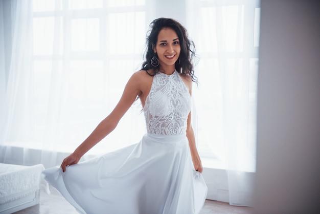 ダンスや豪華なパーティーのためのクラシックなウェア。白いドレスを着た美しい女性が窓から日光の下で白い部屋に立っています。