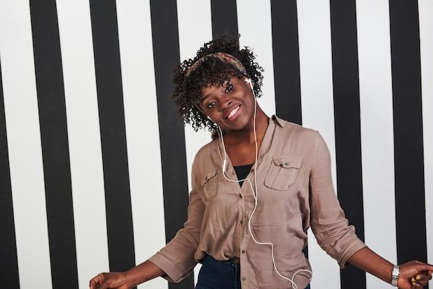 ヘッドフォンで音楽を聴くとそれに踊る女性。微笑んでいるアフロアメリカンガールは、背景に垂直の白と黒の線でスタジオに立っています。