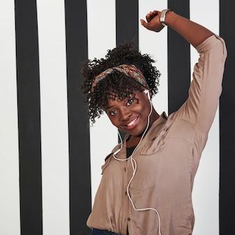 陽気な女性。微笑んでいるアフロアメリカンガールは、背景に垂直の白と黒の線でスタジオに立っています。