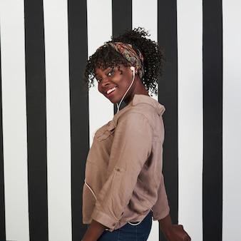 縦の写真。微笑んでいるアフロアメリカンガールは、背景に垂直の白と黒の線でスタジオに立っています。