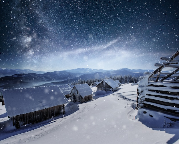 星との夜。クリスマスの風景。山の村の木造住宅。冬の夜の風景