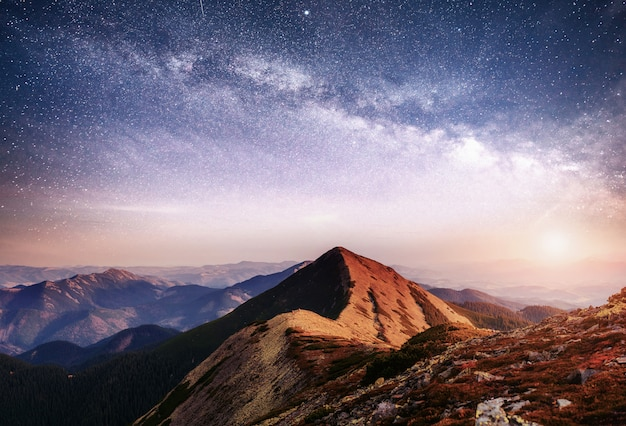 Фантастический пейзаж в горах украины. яркое ночное небо со звездами, туманностью и галактикой.