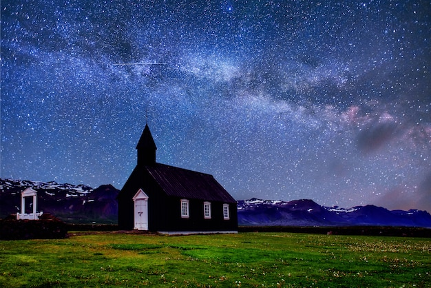 Маунтин-вью исландия. фантастическое звездное небо и млечный путь. красивая черная деревянная церковь в будире