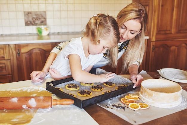 彼女の母親と一緒に幸せな女の子はクッキーを調理します。