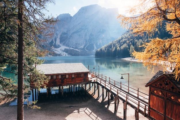 Солнечный свет освещает коричневый дом. хороший пейзаж с горами. туристическое место с деревянным зданием и грушей