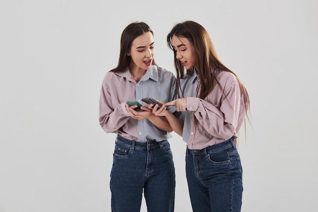 Показывает некоторые интересные вещи в своих телефонах. две сестры-близнецы стоят и позируют