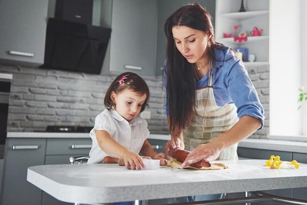 台所で料理をしている母親と一緒に美しい娘
