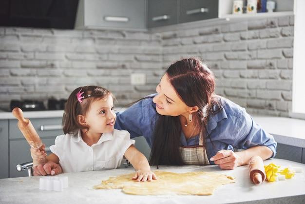 Счастливая семья на кухне. концепция праздника питания. мать и дочь готовят тесто, пекут печенье. счастливая семья в создании куки у себя дома. домашняя еда и маленький помощник