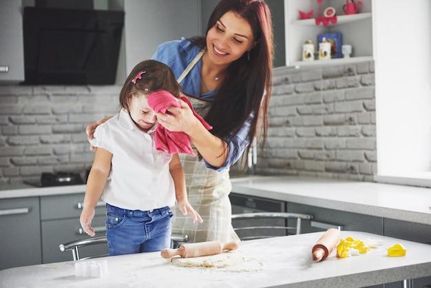 Прекрасная дочь с мамой готовят на кухне