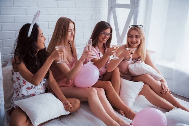 シャンパンは常に重要です。風船とウサギの耳が付いた豪華な白いベッドに座っています。独身の概念