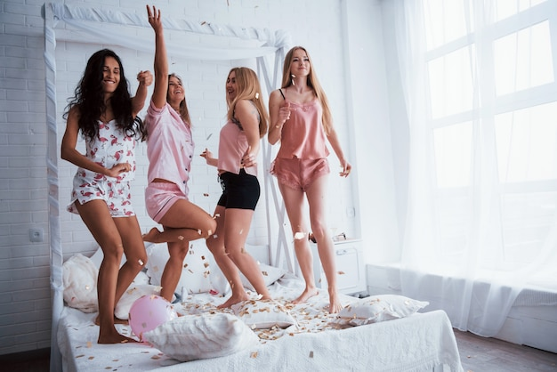 Некоторые сумасшедшие танцы. конфетти в воздухе. молодые девушки развлекаются на белой кровати в красивой комнате