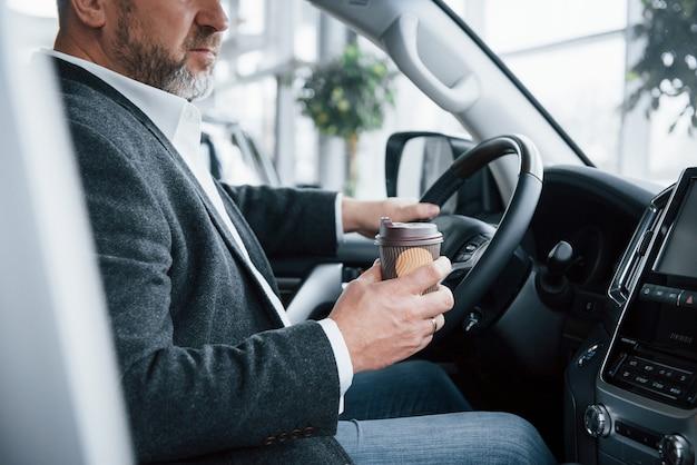 コーヒーを入れて充電する必要があります。現代の車の中の公式の服の上級ビジネスマンの側面図
