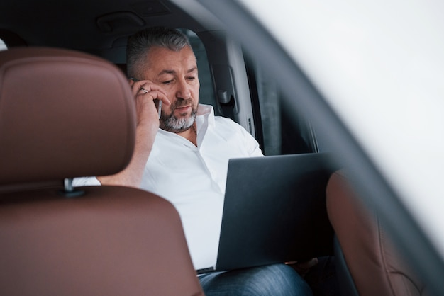 電話で話す。シルバー色のラップトップを使用して車の後ろに取り組んでいます。上級ビジネスマン