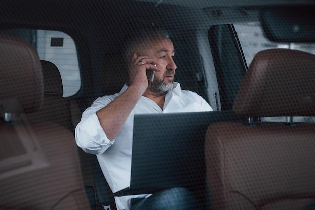 いくつかの取引について話します。シルバー色のラップトップで車の後ろに座っている間にビジネスコールを持っていること