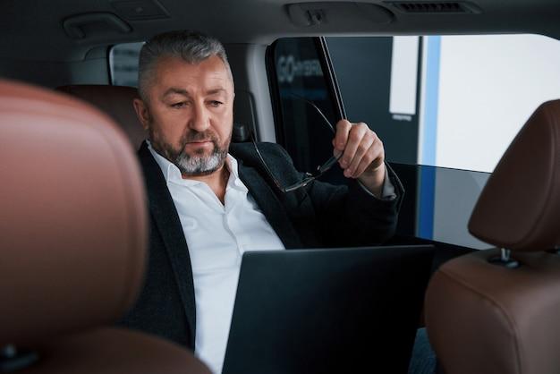 いくつかのドキュメントを読む準備をしています。シルバー色のラップトップを使用して車の後ろに取り組んでいます。上級ビジネスマン
