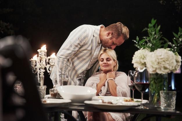 夫は妻にキスします。美しい大人のカップルは夜の時間に豪華なディナーを持っています