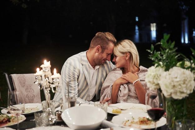 美しい大人のカップルは夜の時間に豪華なディナーを持っています