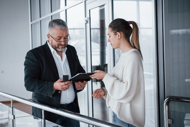 Сотрудничество дает хорошие результаты. девушка показывает документы своему боссу в очках и седой бороде
