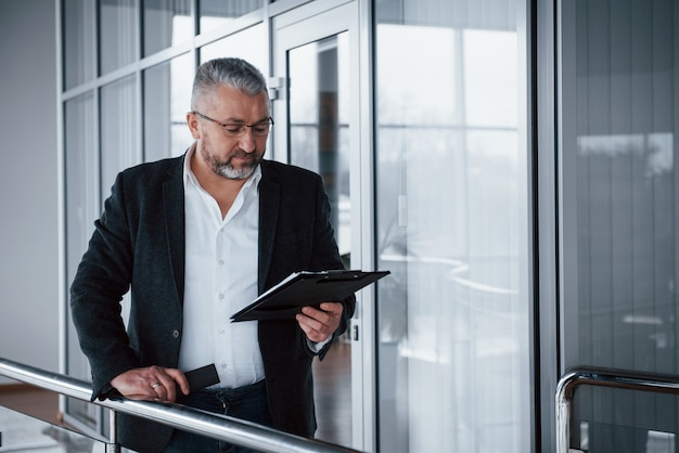 В ожидании работника. фото старшего бизнесмена в просторной комнате с заводами позади. хранение и чтение документов