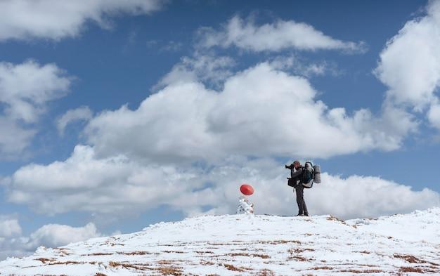 Турист смотрит на пейзаж. фотограф на вершине горы. весенний пейзаж. карпаты, украина, европа