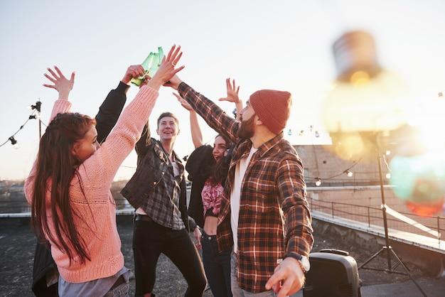 Декоративные праздничные лампочки. отдых на крыше. веселая группа друзей подняла руки с алкоголем