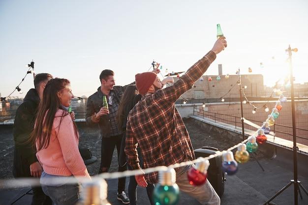 Встречает рассвет. отдых на крыше. веселая группа друзей подняла руки с алкоголем