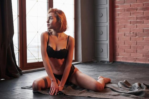 素晴らしい探している女性。窓の近くの部屋の床に座っている下着姿でかわいいセクシーな若い女の子