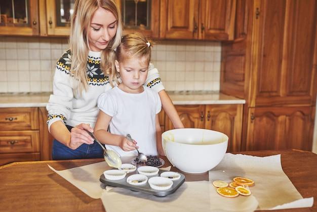 美しい少女はカップケーキを準備しています