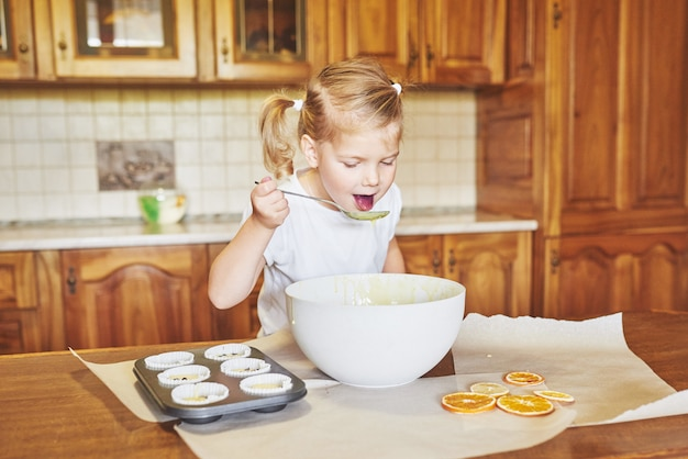 少し良い女の子がおいしいカップケーキを焼く