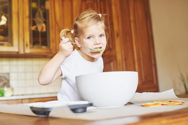 Маленькая хорошая девушка печет вкусные кексы